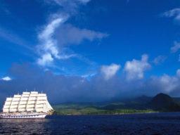 Segelreisen Törnplan Europa ROYAL CLIPPER Produktbild zeigt das 5 Mast Vollschiff komplett besgelt vor einer tropischen Insel.