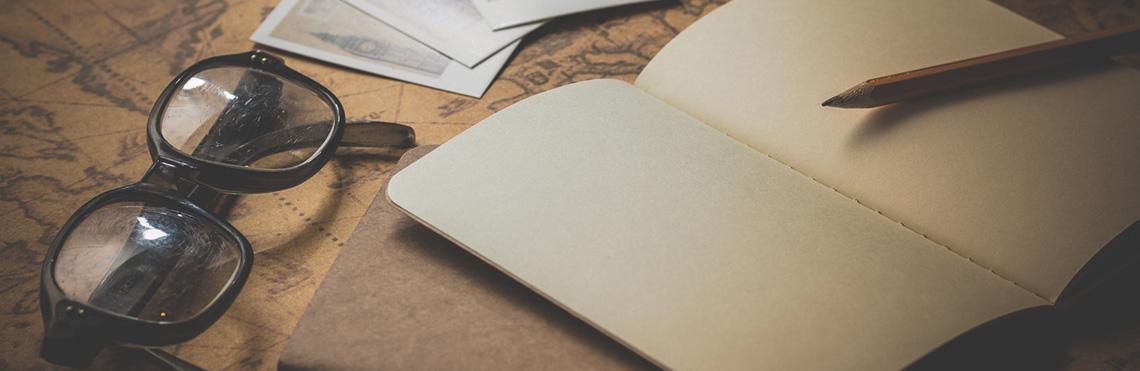 Das Bordmanifest Seitenbild von Windjammer Weltweit zeigt ein gestelltes Foto mit einem leeren Notizbuch und einer Lesebrille