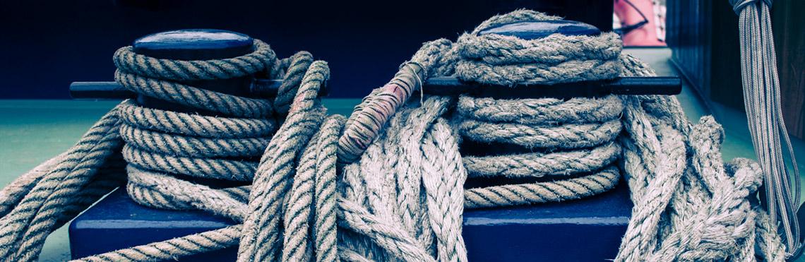 FAQ Segeln Betiragsbild von zeigt zwei mit Seilen umwickelte Festmacher auf einem Traditionssegler
