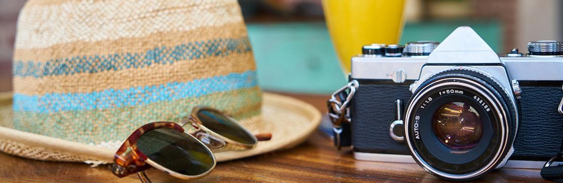Gutscheine und Geschenkgutscheine Seitenbild von Windjammer Weltweit zeigt eine gestellte Szene mit einem Sonnenhut, einer Kamera und einer Sonnenbrille
