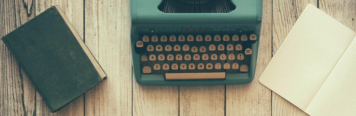 Impressum Beitragsbild zeigt eine alte Schreibmaschine und ein Notizbuch auf einem alten Tisch