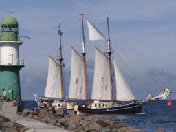 Absegeln Albert Johannes zeigt das Schiff vor einem Leuchturm