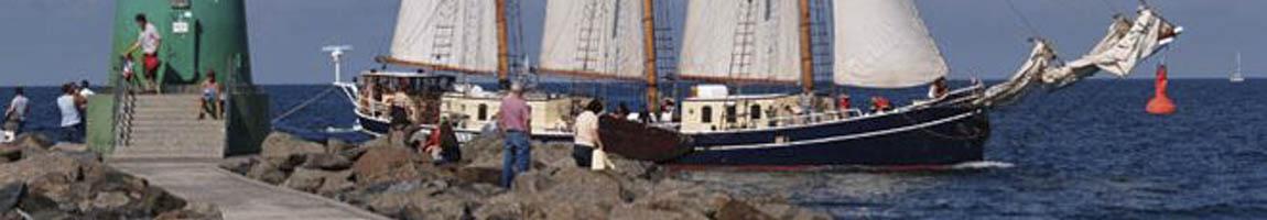 Kojencharter zeigt Segelschiff vor Warnemünde