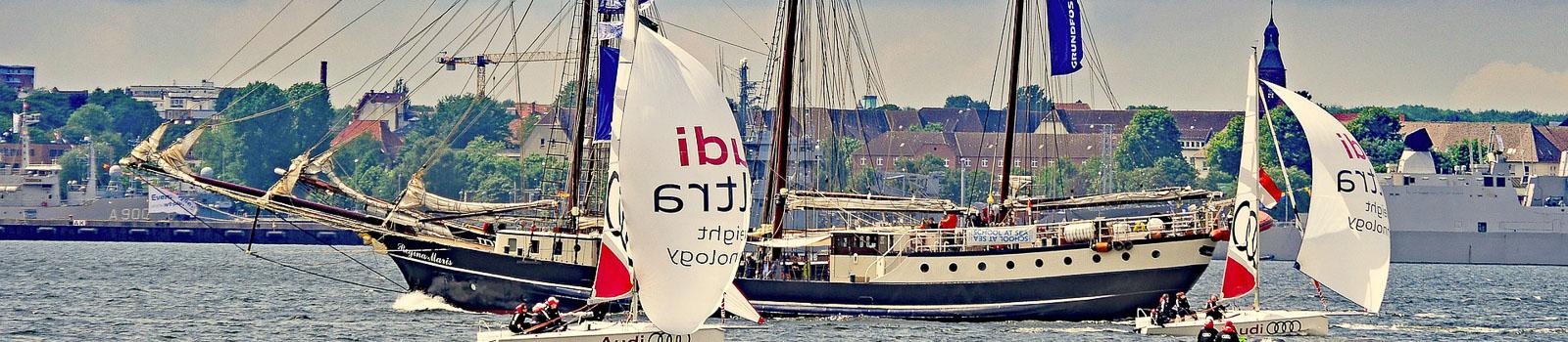 Kieler Woche Bild zeigt Regattasegler und ein Traditionsschiff