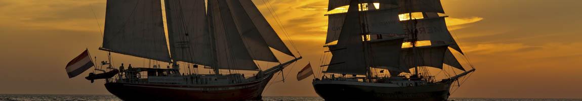 Schiffsreisen mitsegeln Bild zeigt Schiffe im Sonnenuntergang